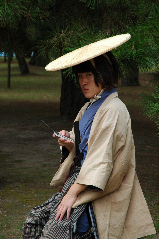 Samurái con un móvil en la mano